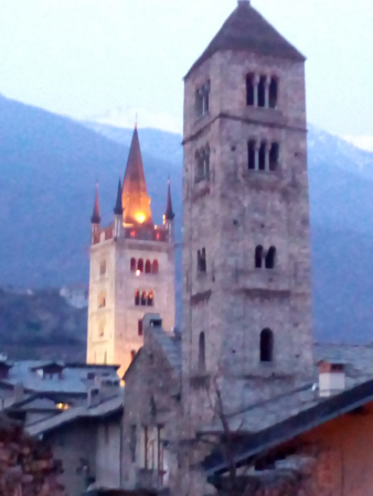 Clocher roman (premier plan) et tour de la cathédrale (2e plan), avec la montagne au fond.