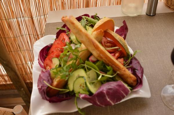 une excellente salade avec de délicieux nems au poulet accompagnée d'un bon verre de vin