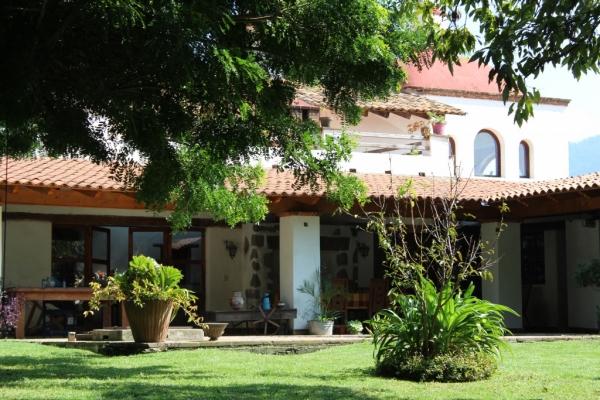 Vue depuis le jardin du préau où sont servis les petits-déjeuners.  En haut à droite, chambre La Cúpula avec vue sur les montagnes.