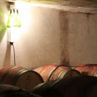 Dans le Chai à barriques : Applique lumineuse originale, en bouteilles de vin.
