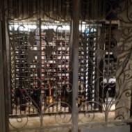 Vieux millésimes produits par la Cave, joliment mis en scène sous grille en ferronnerie d'Art.